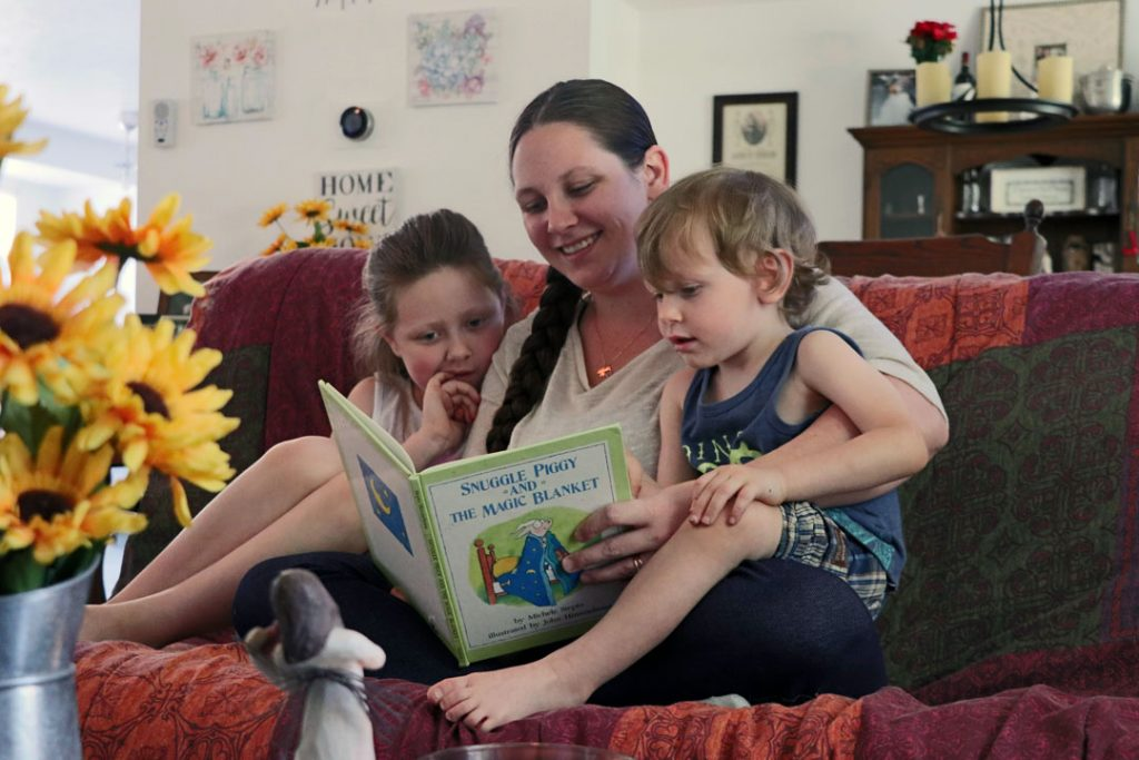 mom with anxiety reading a book to her two kids